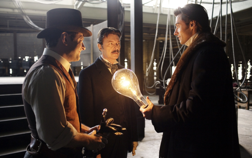 Andy Serkis, David Bowie, and Hugh Jackman in a still from The Prestige. (Warner Bros.)