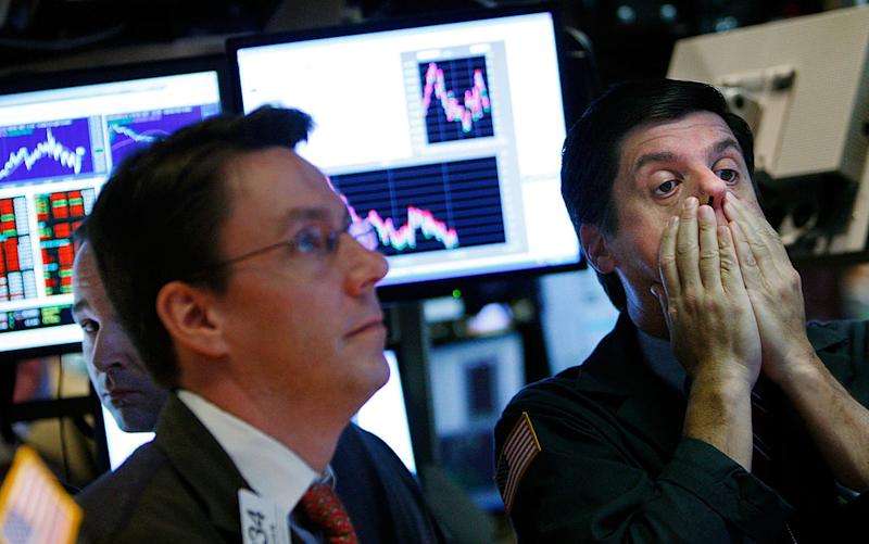 A trader rubs his face while working on the floor of the New York Stock Exchange October 7, 2008 in New York City. Is another recession on the cards? (Photo by Mario Tama/Getty Images)