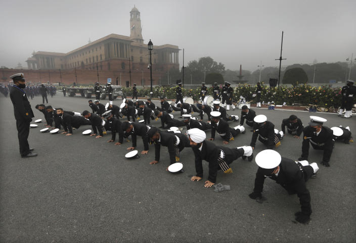 Indian Navy sailors do push-ups to keep themselves warm during rehearsals for the upcoming Republic Day parade at the Raisina hills, the government seat of power, in New Delhi, India, Monday, Jan. 18, 2021. Republic Day marks the anniversary of the adoption of the country's constitution on Jan. 26, 1950. Thousands congregate on Rajpath, a ceremonial boulevard in New Delhi, to watch a flamboyant display of the country's military power and cultural diversity. (AP Photo/Manish Swarup)