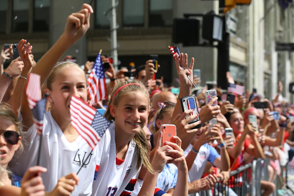 Fans celebrate by taking photos and waving flags as members of the the U.S. women's soccer team pass by during a ticker tape parade along the Canyon of Heroes, Wednesday, July 10, 2019, in New York. (Photo: Gordon Donovan/Yahoo News)