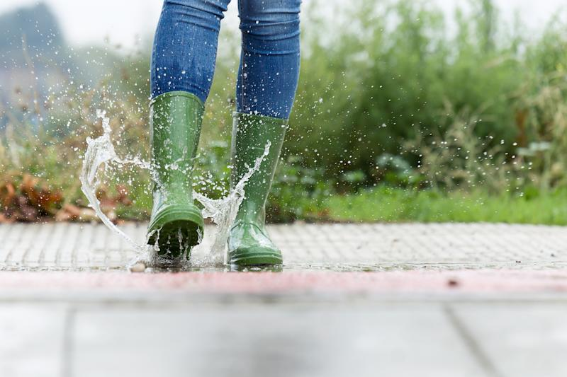Close-up of woman in green rubber boots jumping on the puddle water in the street.