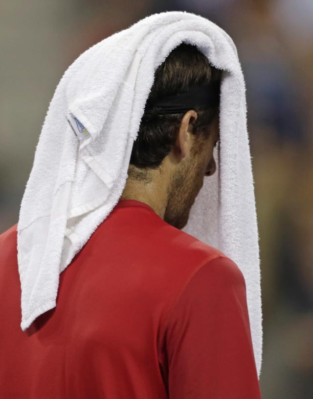 Juan Martin del Potro, of Argentina, walks with a towel over his head after losing a point in the second game against Novak Djokovic, of Serbia, in the quarterfinal round of play at the U.S. Open tennis tournament, Thursday, Sept. 6, 2012, in New York. (AP Photo/Charles Krupa)
