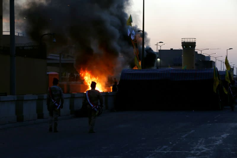 Iraqi security forces walk as the Hashd al-Shaabi (paramilitary forces) fighters set the U.S. Embassy wall on fire, as they protest to condemn air strikes on their bases, in Baghdad
