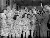 <p>A group of young choir girls being conducted by their teacher. </p>