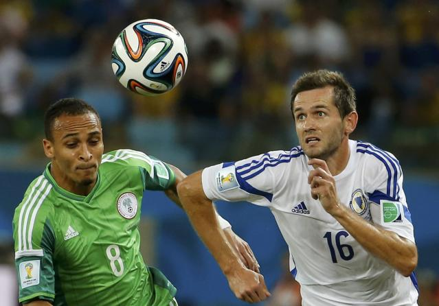 Nigeria's Peter Odemwingie runs for the ball with Bosnia's Senad Lulic during their 2014 World Cup Group F soccer match at the Pantanal arena in Cuiaba June 21, 2014. REUTERS/Eric Gaillard (BRAZIL - Tags: SOCCER SPORT WORLD CUP)