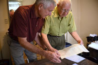 In this Saturday, July 17, 2021, photo, Dave Ware, left, and his father, Fred Ware, look over a deed and copy of a covenant for their home in Manchester, Conn. Fred and Dave Ware recently found a whites-only covenant on his property dating back to 1942 when researching the title chain. Upon finding the covenant, Dave Ware, who grew up in the home, reached out to state lawmakers and helped get a bill passed that strips these covenants on properties. (AP Photo/Jessica Hill)