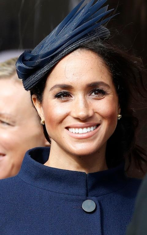 Meghan, Duchess of Sussex, smiles as she waits for the bridal procession at the wedding of Princess Eugenie of York and Jack Brooksbank in St George's Chapel, Windsor Castle - Credit: Alastair Grant/AP