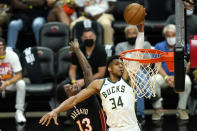 Milwaukee Bucks forward Giannis Antetokounmpo (34) shoots as Miami Heat center Bam Adebayo (13) defends during the second half of Game 4 of an NBA basketball first-round playoff series, Saturday, May 29, 2021, in Miami. (AP Photo/Lynne Sladky)