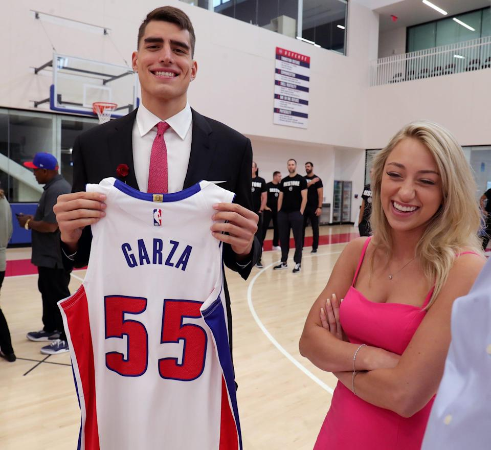 Pistons second-round draft pick Luka Garza holds upholds up his game jersey with his girlfriend, Maggie Mynderse, after the news conference on Friday, July 30, 2021, at the team's practice facility in Detroit.