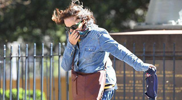 A woman struggles to walk in the wild winds. Picture: AAP