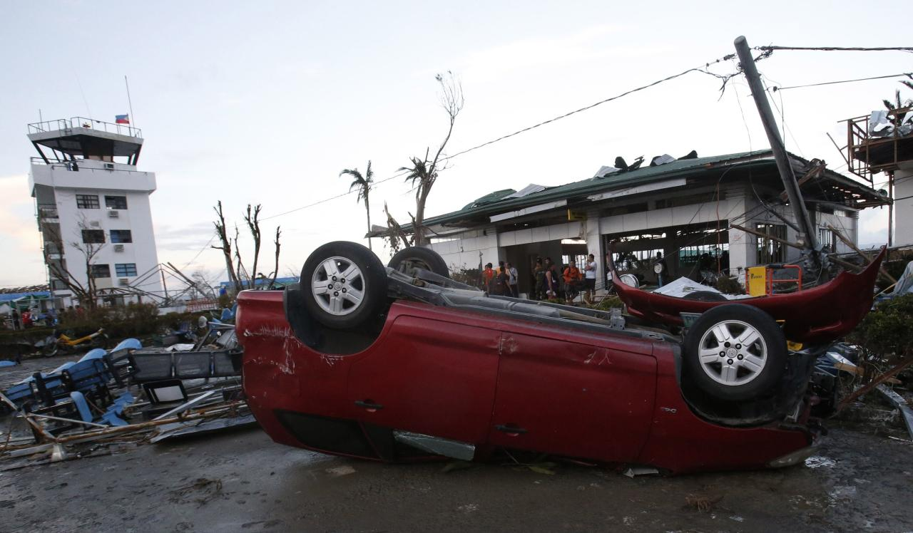 A car lies upside down outside an airport after super Typhoon Haiyan battered Tacloban city in central Philippines November 9, 2013. Possibly the strongest typhoon ever to hit land devastated the central Philippine city of Tacloban, killing at least 100 people, turning houses into rubble and leveling the airport in a surge of flood water and high wind, officials said on Saturday. The toll of death and damage from Typhoon Haiyan on Friday is expected to rise sharply as rescue workers and soldiers reach areas cut off by the massive, fast-moving storm which weakened to a category 4 on Saturday. REUTERS/Erik De Castro (PHILIPPINES - Tags: DISASTER ENVIRONMENT)