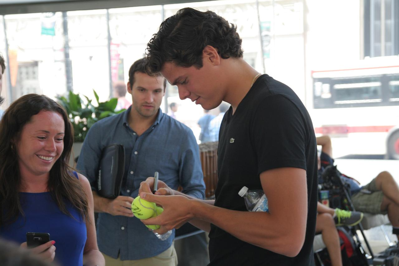 Milos Raonic signs a tennis ball for a fan at Commerce Court in Toronto. (Photo Courtesy Alex Jones Photography)