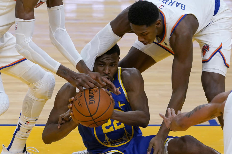 Golden State Warriors forward Andrew Wiggins, bottom, passes the ball as New York Knicks guard RJ Barrett, top right, defends during the first half of an NBA basketball game in San Francisco, Thursday, Jan. 21, 2021. (AP Photo/Jeff Chiu)