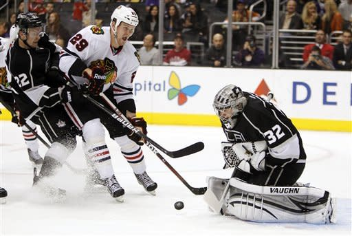 Los Angeles Kings goalie Jonathan Quick (32) stops Chicago Blackhawks left wing Bryan Bickell (29) with Kings center Trevor Lewis (22) defending on a rebound of the puck during the first period of an NHL hockey game in Los Angeles, Saturday, Feb. 25, 2012. (AP Photo/Alex Gallardo)