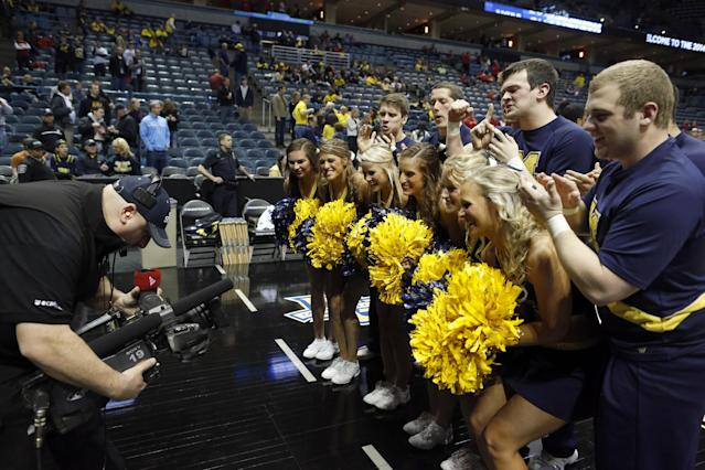 Michigan cheerleaders pose for the TV camera before a third-round game of the NCAA college basketball tournament between the Michigan and the Texas Saturday, March 22, 2014, in Milwaukee. (AP Photo/Jeffrey Phelps)