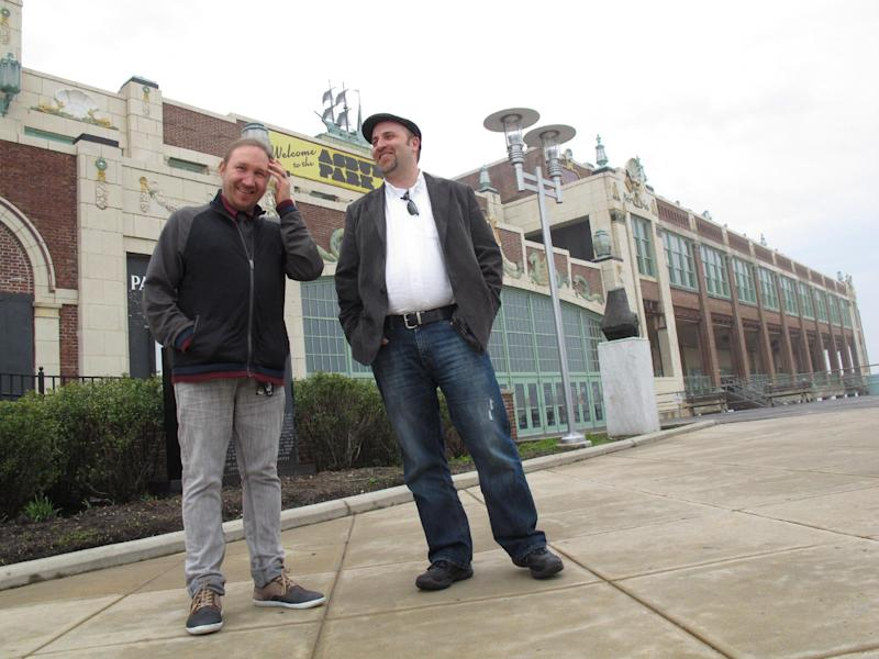 In this May 9, 2012 photo, Christian McKnight, left, senior talent buyer for concert promoter Live nation, discusses the upcoming Bamboozle Festival with Scott O'Donnell, the company's executive director of programming and festivals, in front of the Paramount Theater in Asbury Park, N.J. The theater is one of seven stages that will be used for the May 18-20 concert, headlined by Bon Jovi. (AP Photo/Wayne Parry)