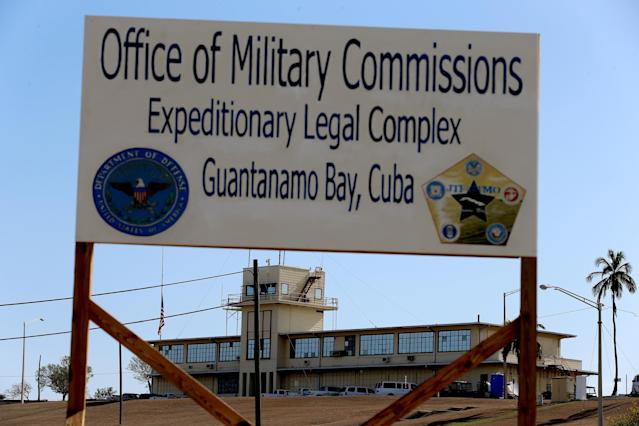 "GUANTANAMO BAY, CUBA - JUNE 25: (EDITORS NOTE: Image has been reviewed by the U.S. Military prior to transmission.) A sign reading, ""Office of Military Commissions Expeditionary Legal Complex Guantanamo Bay, Cuba"" stands close to where pre-trial hearings are being held for the detainees at the military prison on June 25, 2013 in Guantanamo Bay, Cuba. President Barack Obama has recently spoken again about closing the prison which has been used to hold prisoners from the invasion of Afghanistan and the war on terror since early 2002. (Photo by Joe Raedle/Getty Images)"