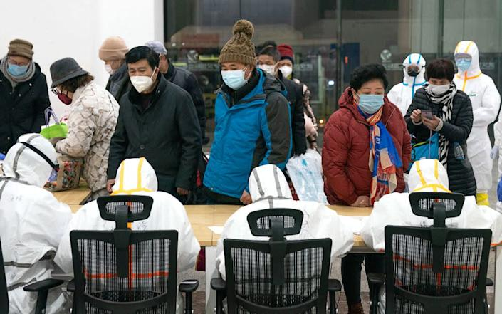 Medical workers help patients infected with coronavirus at a makeshift hospital in Wuhan, central China's Hubei Province. | Xinhua News Agency/Contributor