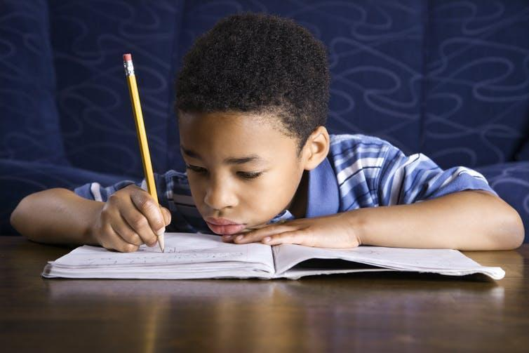 Boy writing with pencil in notebook