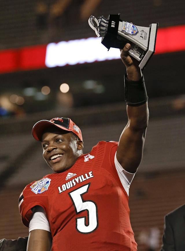 Louisville quarterback Teddy Bridgewater (5) holds up the MVP trophy after Louisville defeated Miami 36-9 in the Russell Athletic Bowl NCAA college football game in Orlando, Fla., Saturday, Dec. 28, 2013.(AP Photo/John Raoux)