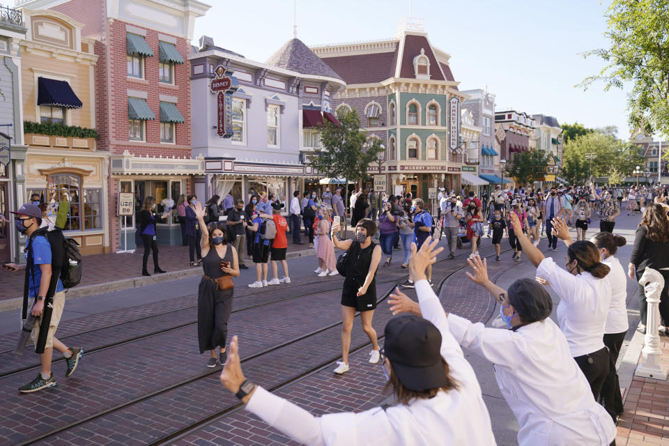 FILE - In this Friday, April 30, 2021, file photo, guests walk down Main Street USA at Disneyland in Anaheim, Calif. California's top health official says the state will no longer require social distancing and will allow full capacity for businesses when the state reopens on June 15. State health director Dr. Mark Ghaly said Friday, May 21, 2021, that dramatically lower virus cases and increasing vaccinations mean it's safe for the state to remove nearly all restrictions next month. (AP Photo/Jae Hong, File)