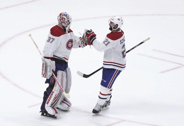 Montreal Canadiens goaltender Antti Niemi (37) is greeted by defenseman David Schlemko (21) after the Canadiens' 4-3 win over the Detroit Red Wings in an NHL hockey game Thursday, April 5, 2018, in Detroit. (AP Photo/Carlos Osorio)