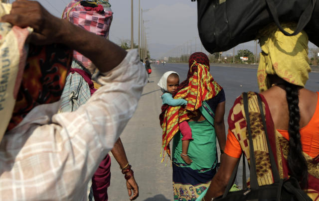 """Migrant workers walk to their villages along the Mumbai Pune highway during 21 day countrywide lockdown in Mumbai, India, Sunday, March 29, 2020. Indian Prime Minister Narendra Modi apologized to the public on Sunday for imposing a three-week national lockdown, calling it harsh but """"needed to win"""" the battle against the coronavirus pandemic. The new coronavirus causes mild or moderate symptoms for most people, but for some, especially older adults and people with existing health problems, it can cause more severe illness or death. (AP Photo/Rajanish Kakade)"""
