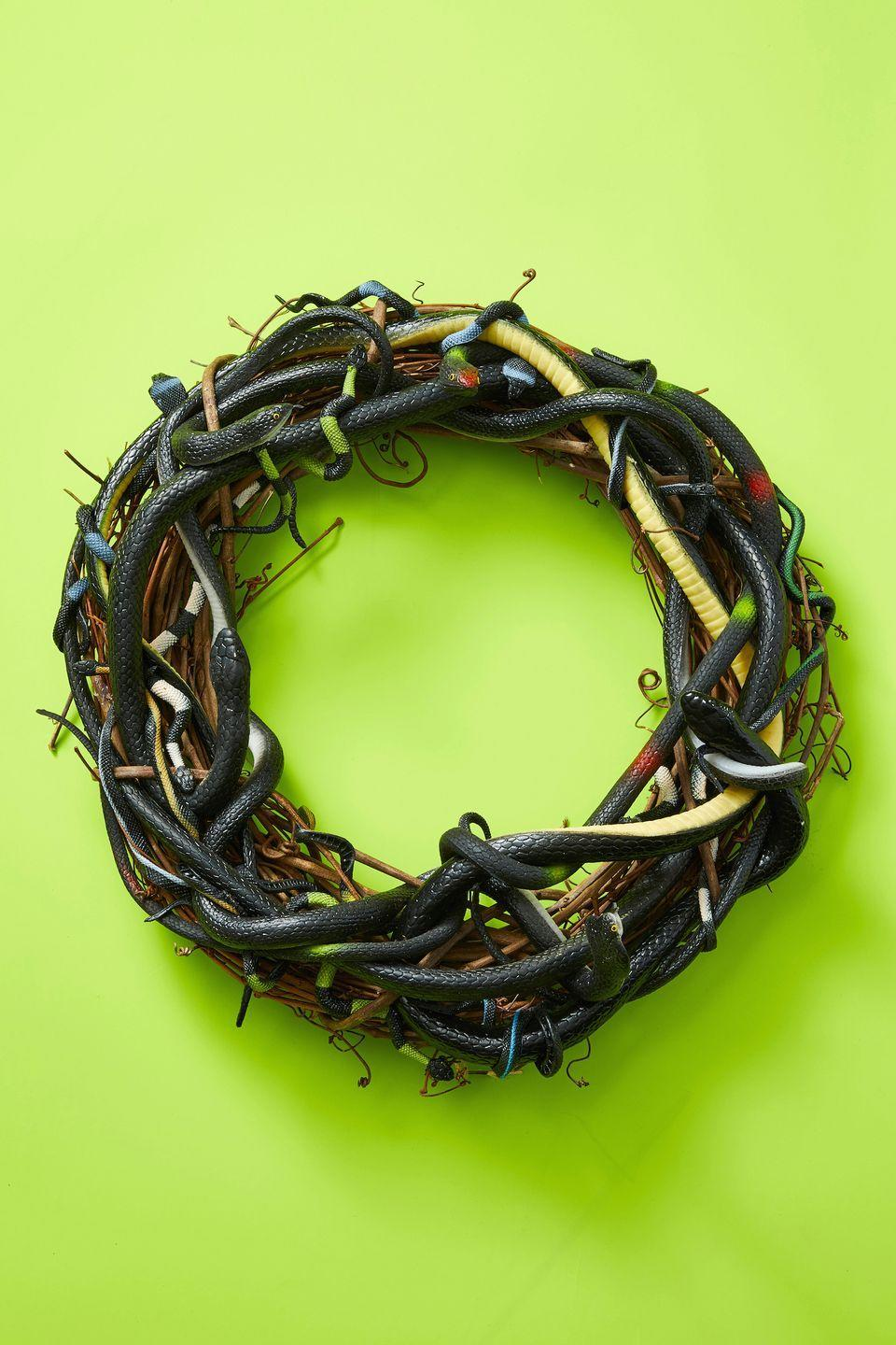 """<p>Spook the neighbors with this snake-laden wreath. To make it, weave plastic snakes, from large to small, between the wreath's twigs, repeating until you use all of the rubber snakes. Use hot glue as needed to attach them to the wreath. </p><p><a class=""""link rapid-noclick-resp"""" href=""""https://www.amazon.com/Fun-Central-Rubber-Snakes-Garden/dp/B01C4OTKAU/?tag=syn-yahoo-20&ascsubtag=%5Bartid%7C10055.g.421%5Bsrc%7Cyahoo-us"""" rel=""""nofollow noopener"""" target=""""_blank"""" data-ylk=""""slk:SHOP RUBBER SNAKES"""">SHOP RUBBER SNAKES</a> </p><p><strong>RELATED</strong>: <a href=""""https://www.goodhousekeeping.com/home/craft-ideas/how-to/g859/fall-wreaths/"""" rel=""""nofollow noopener"""" target=""""_blank"""" data-ylk=""""slk:30+ Fall Wreaths to Welcome the Season in Style"""" class=""""link rapid-noclick-resp"""">30+ Fall Wreaths to Welcome the Season in Style</a></p>"""