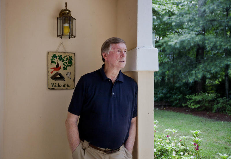 """In this Tuesday, July 9, 2013 photo, Lamar Kellett stands in the entryway to his house, in Nelson, Ga. Kellett opposes a recent city law requiring every head of household to own a gun and ammunition. City leaders and the sole police officer in town said when the ordinance was passed that they had no intention of enforcing it. Several weeks after, Kellett went out and spent nearly $700 on a handgun and ammunition. """"How does a citizen like myself know that that will be true in the future or even next week?"""" Kellett said of the council's decision not to enforce the law. As the national debate over gun control swirled in the spring, the tiny Georgia city made a statement supporting gun rights by passing an ordinance requiring gun ownership. Now a national gun control group is using a lawsuit challenging that law to send a message of its own. (AP Photo/David Goldman)"""
