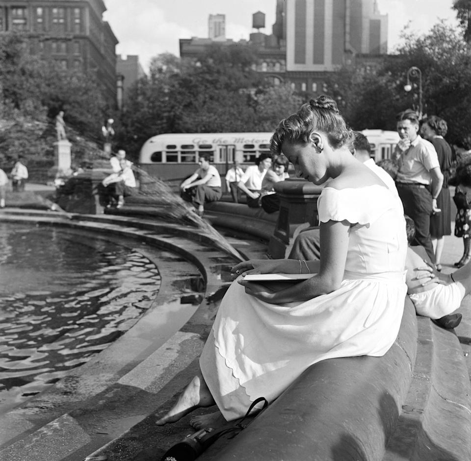A woman reads a book next to the Washington Square Park Fountain in the late 1940s. In 2009, the fountain underwent a restoration, and was moved ten feet in order to align with the Washington Square Arch.