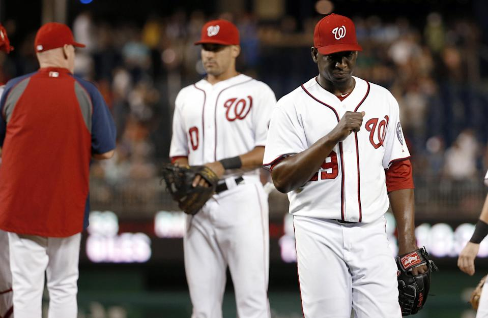 Washington Nationals relief pitcher Rafael Soriano, right, walks to the dugout after being relieved during the ninth inning of a baseball game against the Philadelphia Phillies at Nationals Park, Friday, Sept. 5, 2014, in Washington. The Phillies won 9-8 in 11 innings. (AP Photo/Alex Brandon)