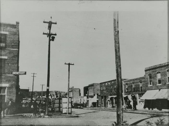 The image shows many buildings later destroyed in the 1921 Tulsa Race Massacre. The building on the far left is the Williams Building. The sign for dentist J. J. McKeever is visible. On the right side of the street (looking North toward Brickyard Hill) is the Bryant Building, Howard Building, Hardy Building, Gist Building, Nichols Building and the Dreamland Theatre.
