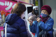 A shopper wearing a protective mask to help curb the spread of the coronavirus uses a mirror as she tries on a hat in a shopping street in Tokyo Thursday, Jan. 14, 2021. The Japanese capital confirmed more than 1500 new coronavirus cases on Thursday. (AP Photo/Eugene Hoshiko)