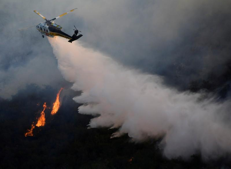 FILE PHOTO: A firefighting helicopter makes a water drop on the Getty Fire as it burns in the hills of West Los Angeles, California