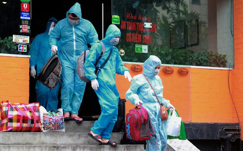 People walk toward an ambulance to be driven to a hospital for quarantine relating to a suspected case in Hanoi, Vietnam - AP