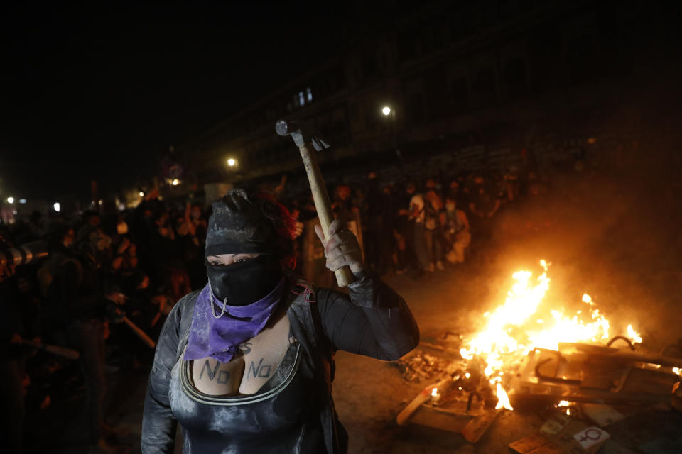 A demonstrator brandishes a hammer as other light a fire in front of the National Palace during a march to commemorate International Women's Day and protesting against gender violence, in Mexico City, Monday, March 8, 2021. (AP Photo/Rebecca Blackwell)