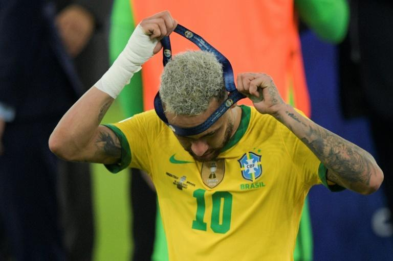 Neymar takes off his runner-up medal after Brazil lost the Copa America final 1-0 to arch rivals Argentina