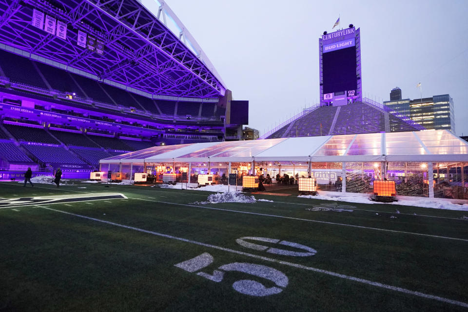 """People eat dinner in an outdoor dining tent set up near the 50-yard line at Lumen Field, the home of the Seattle Seahawks NFL football team, Thursday, Feb. 18, 2021, in Seattle. The """"Field To Table"""" event was the first night of several weeks of dates that offer four-course meals cooked by local chefs and served on the field at tables socially distanced as a precaution against the COVID-19 pandemic, which has severely limited options for dining out at restaurants in the area. (AP Photo/Ted S. Warren)"""