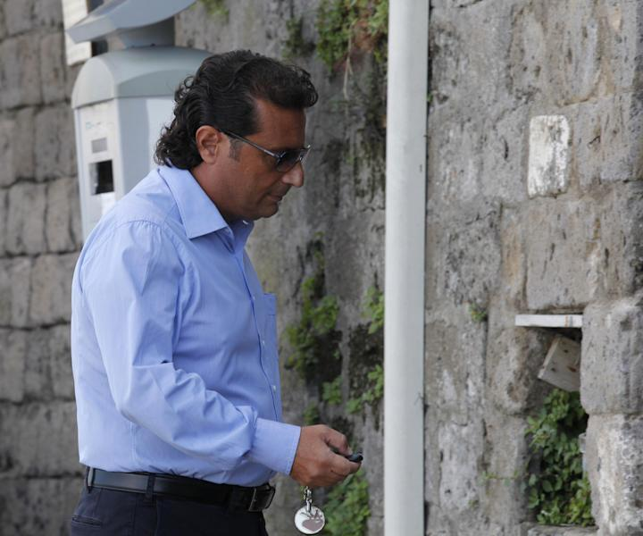 Francesco Schettino, the former captain of Costa Concordia, leaves his home in Meta Di Sorrento, near Naples, Sunday, Oct. 14, 2012. The first hearing of the trial for the Jan. 13 tragedy, where 32 people died after the luxury cruise Costa Concordia was forced to evacuate some 4,200 passengers as it hit a rock while passing too close to the Giglio Island, is taking place in Grosseto Monday. Captain Francesco Schettino, who was blamed for both the accident and for leaving the ship before the passengers, is scheduled to attend the hearing. (AP Photo/Salvatore Laporta)