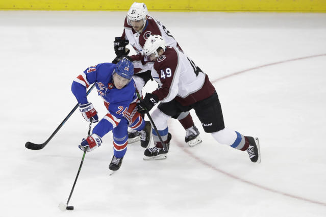 New York Rangers' Kaapo Kakko (24) passes the puck away from Colorado Avalanche's Samuel Girard (49) and Matt Nieto (83) during the third period of an NHL hockey game Tuesday, Jan. 7, 2020, in New York. The Rangers won 5-3. (AP Photo/Frank Franklin II)