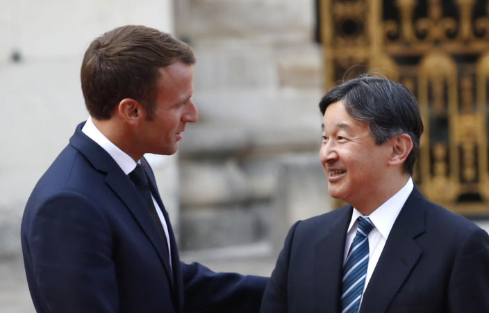 FILE - In this Sept. 12, 2018, file photo, Japan's Crown Prince Naruhito, right, is greeted by French President Emmanuel Macron before a meeting at the Chateau de Versailles, west of Paris. On May 1, 2019, when Crown Prince Naruhito becomes, by official Japanese count, the nation's 126th person to sit on the Chrysanthemum Throne since 660 B.C., he will be ceremonially armed with the glittering, ancient imperial regalia of sword, mirror and jewel. (AP Photo/Christophe Ena, File)
