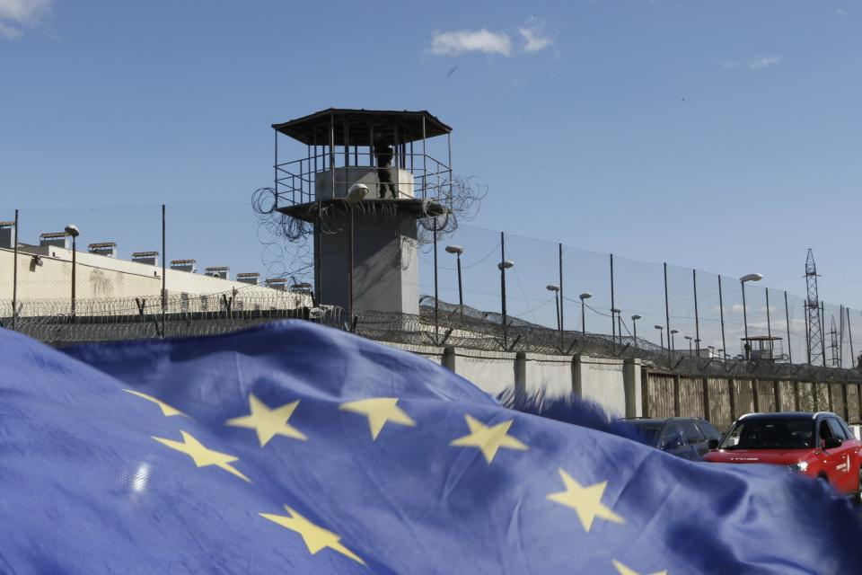 A soldier stands guard on a prison's watchtower as Georgian opposition supporters of former president Mikheil Saakashvili hold an EU flag as they gather for a rally in his support in front of the prison where former president is being held, in Rustavi, about 20 km from the capital Tbilisi, Georgia, Monday, Oct. 4, 2021. Saakashvili was detained in Tbilisi on Saturday, Oct. 1, 2021. Georgia earlier declared Saakashvili wanted as a person convicted in absentia in several criminal cases and treated as a suspect in some others. Georgian authorities have warned repeatedly that he would be detained immediately once over the border. (AP Photo/Shakh Aivazov)