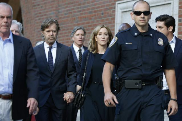 Felicity Huffman leaves federal court with her husband William H. Macy, left, and her brother Moore Huffman Jr., rear center, after she was sentenced in a nationwide college admissions bribery scandal, Friday, Sept. 13, 2019, in Boston. (AP Photo/Michael Dwyer)