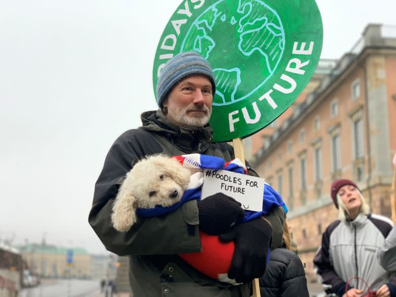 "Hakan Ottosson and his poodle Luna protest during the ""Fridays For Future"" climate strike outside the Parliament in Stockholm"