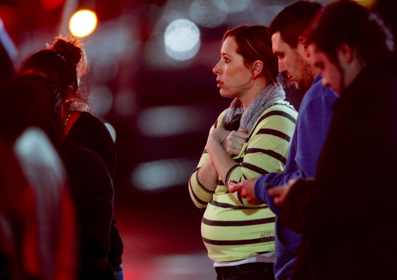 Onlookers observe the scene outside Clackamas Town Center in Clackamas, Ore., where a shooting occurred Tuesday, Dec. 11, 2012. A gunman opened fire in the Portland, Ore., area shopping mall Tuesday, killing at least one person and wounding an unknown number of others, sheriff's deputies said. (AP Photo/The Oregonian, Bruce Ely) MAGS OUT; TV OUT; LOCAL TV OUT; LOCAL INTERNET OUT; THE MERCURY OUT; WILLAMETTE WEEK OUT; PAMPLIN MEDIA GROUP OUT