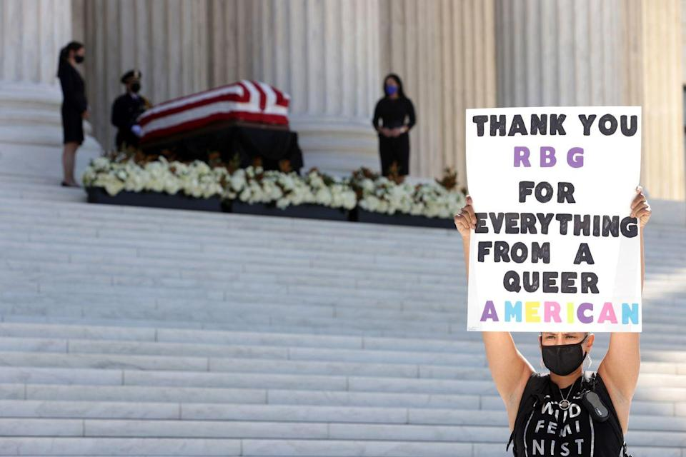 <p>A woman holds up a sign as she pays respect to Associate Justice Ruth Bader Ginsburg as her flag-draped casket rests on the Lincoln catafalque on the west front of the U.S. Supreme Court September 23, 2020 in Washington, DC.</p>