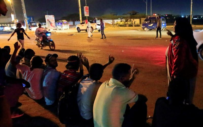 Civilians gather near the area where gunmen opened fire outside buildings used by Sudan's National Intelligence and Security Service in Khartoum