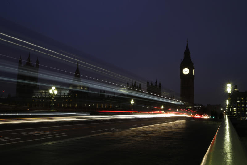 Traffic passes over Westminster Bridge towards the Palace of Westminster with the Elizabeth Tower containing Big Ben, as the daily commute for many workers starts just before sunrise in London, Wednesday, Oct. 26, 2016. (AP Photo/Alastair Grant)