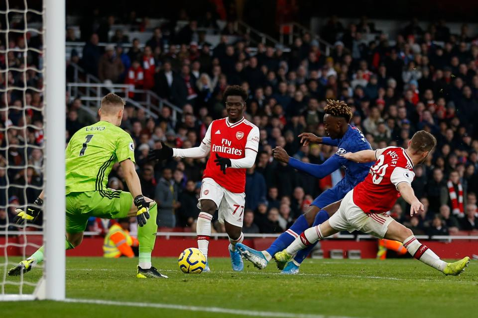 Chelsea's English striker Tammy Abraham  (2R) scores their second goal to take the lead 1-2 during the English Premier League football match between Arsenal and Chelsea at the Emirates Stadium in London on December 29, 2019. (Photo by Ian KINGTON / IKIMAGES / AFP) / RESTRICTED TO EDITORIAL USE. No use with unauthorized audio, video, data, fixture lists, club/league logos or 'live' services. Online in-match use limited to 45 images, no video emulation. No use in betting, games or single club/league/player publications. (Photo by IAN KINGTON/IKIMAGES/AFP via Getty Images)
