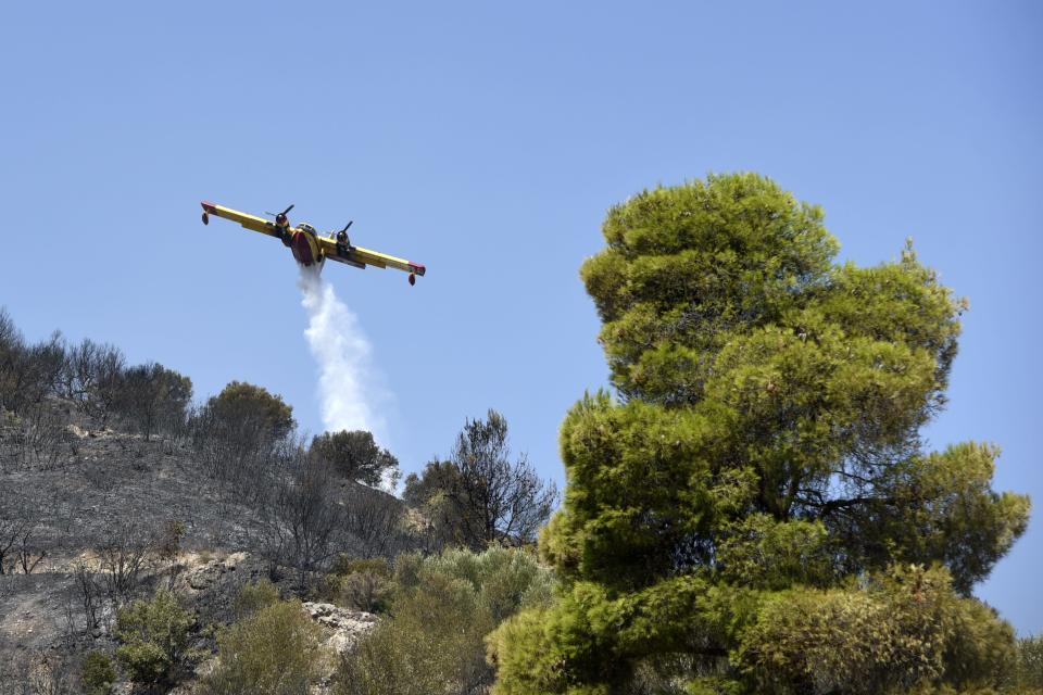 An aircraft drops water in Lampiri village, east of Patras city, Greece, Sunday, Aug. 1, 2021. A wildfire that broke out Saturday in western Greece forced the evacuation of four villages and people on a beach by the Fire Service, the Coast Guard and private boats, authorities said. (AP Photo/Andreas Alexopoulos)